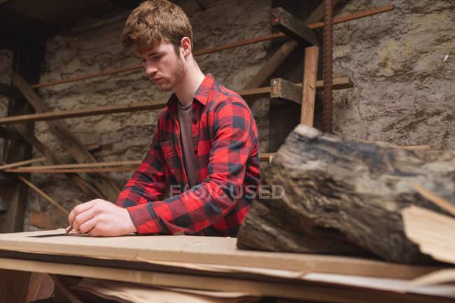 Молодой плотник работает в мастерской — стоковое фото