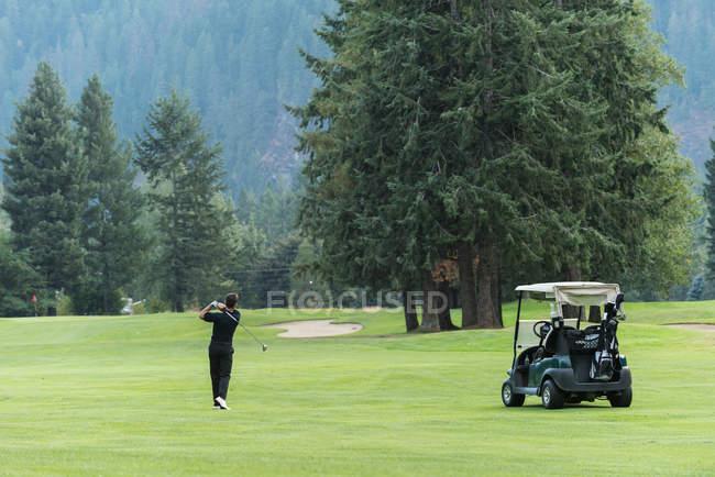 Golfer schlägt einen Golfschlag auf dem Platz — Stockfoto