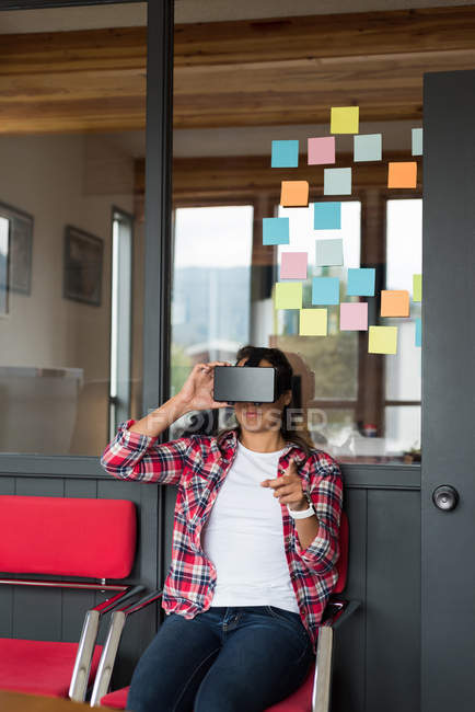 Female executive sitting on chair and using virtual reality headset in office — Stock Photo