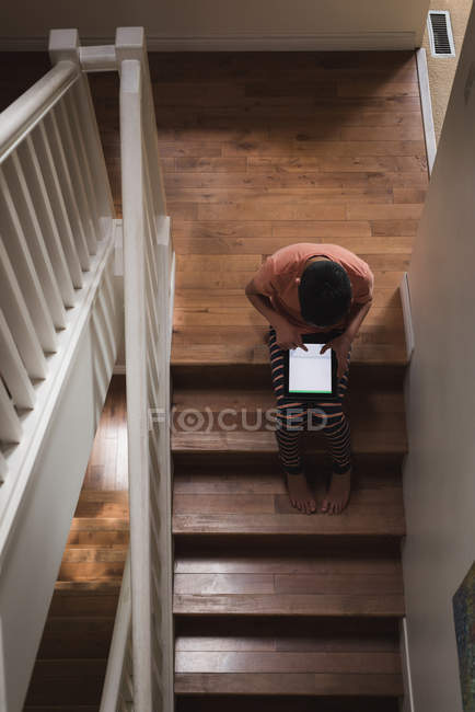 Boy using digital tablet on stairs at home — Stock Photo