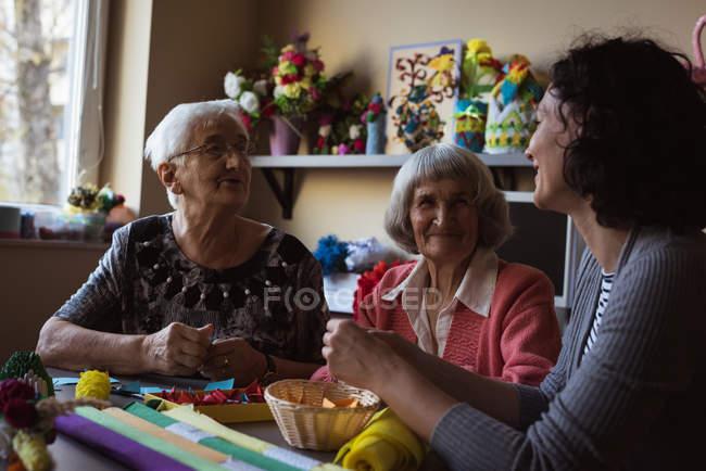 Два старших женщин, взаимодействующих с сторожа в доме престарелых — стоковое фото