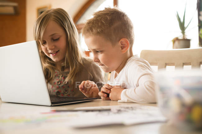Children using laptop together in kitchen at home — Stock Photo