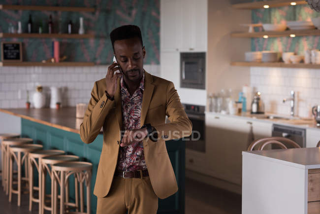 Businessman looking at smart watch while talking on mobile phone in office cafeteria — Stock Photo