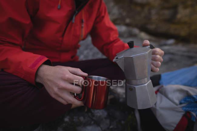 Gros plan de la main du randonneur versant de la boisson dans une tasse — Photo de stock