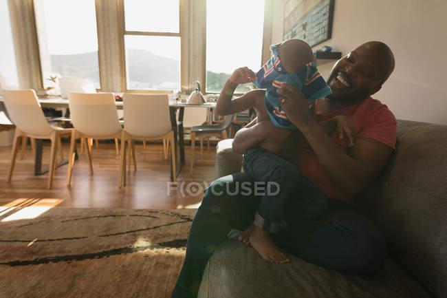 Отец сын помогает ношение одежды в гостиной дома — стоковое фото