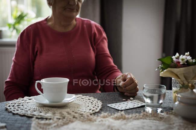 Sección media de la mujer mayor mirando medicamentos en la sala de estar - foto de stock