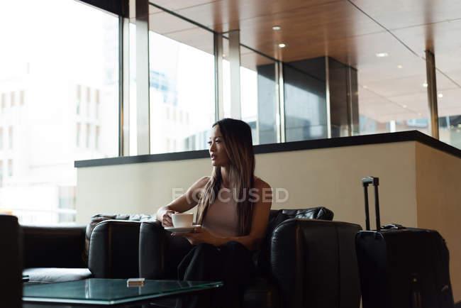 Бізнес-леді сидячи поодинці фотографіях хтось дивитися вбік маючи кави в фойє — стокове фото