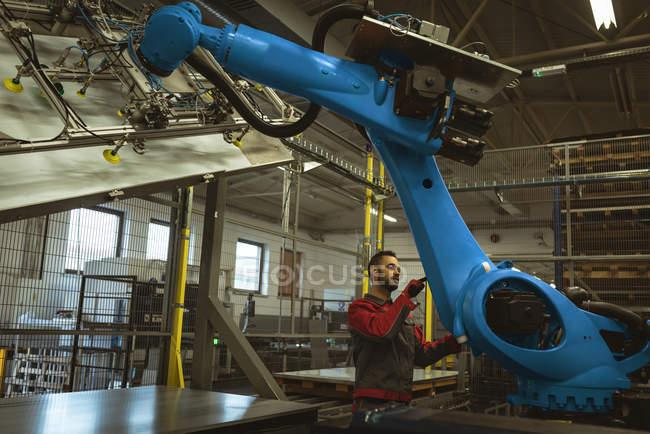 Чоловічий працівник перевірка robotic машина на заводі — стокове фото