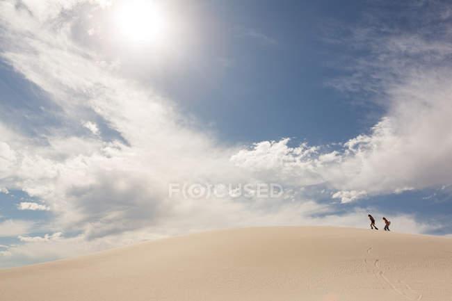 Couple avec plateau de sable marchant dans une dune de sable par une journée ensoleillée — Photo de stock