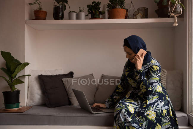 Мусульманская женщина разговаривает по телефону, используя ноутбук дома — стоковое фото