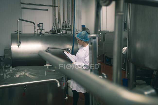 Жіночий працівник моніторингу машина на заводі — стокове фото