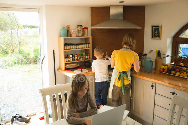 Mother and son preparing food while daughter using laptop in background in kitchen at home — Stock Photo