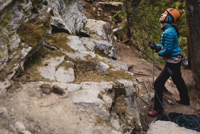 Femme déterminée à escalader la falaise rocheuse — Photo de stock