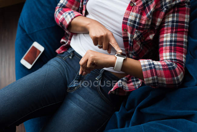 Female executive sitting on arm chair and using smartwatch in office — Stock Photo