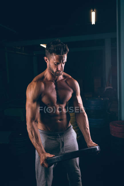 Muscular man exercising with weight plate in fitness studio — Stock Photo