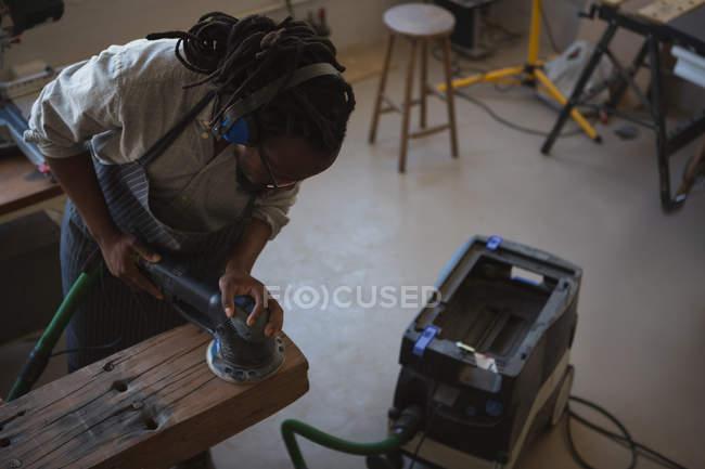 Высокий угол зрения Карпентер, выравнивание древесины с полировочной машиной в мастерской — стоковое фото