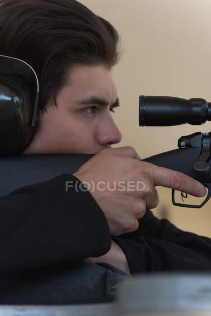Close-up do homem apontando o rifle sniper no alvo no tiro ao alvo — Fotografia de Stock