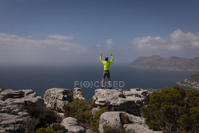 Hiker standing at the top of mountain with raised hands on a sunny day — Stock Photo