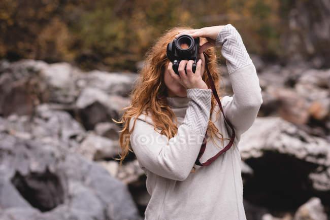 Donna dai capelli rossi che fotografa nella foresta — Foto stock