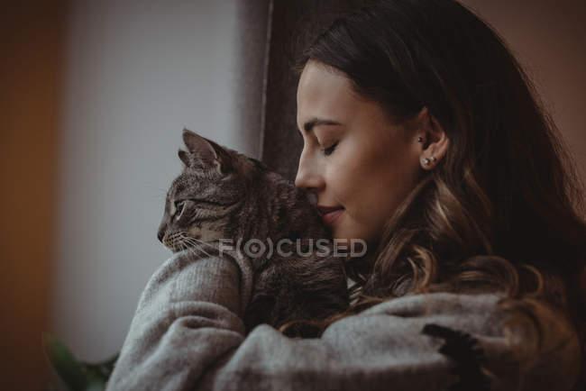 Крупный план красивой женщины, нюхающей своего домашнего кота дома — стоковое фото