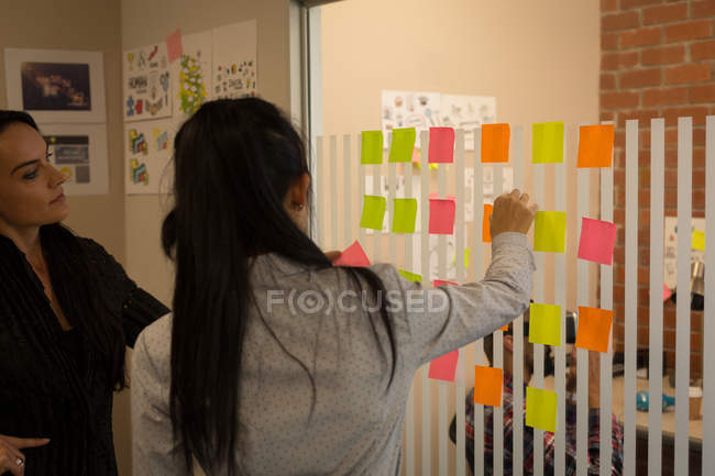 Female business colleagues discussing over sticky notes in office — Stock Photo