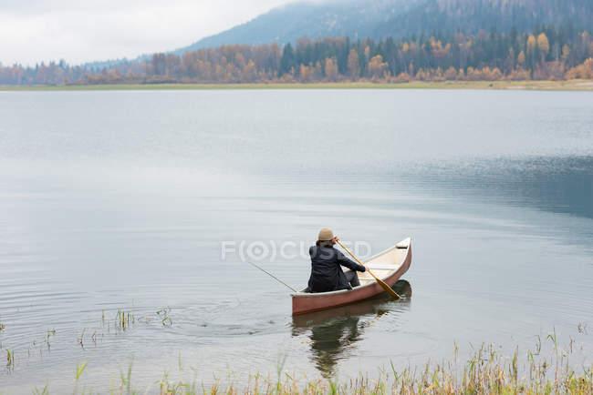 Homme aviron canot dans la rivière silencieuse — Photo de stock