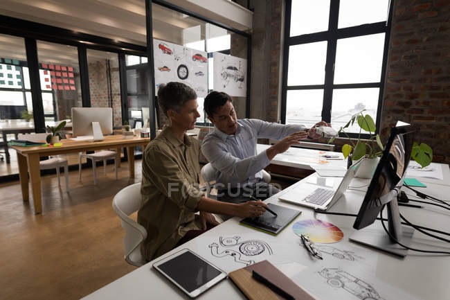 Business colleagues discussing over car model in office. — Stock Photo