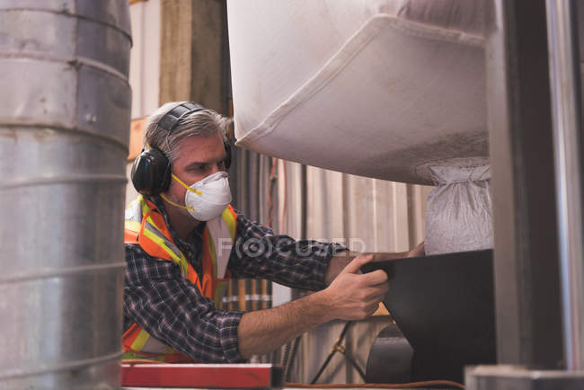 Man in protective workwear refining grain in factory — Stock Photo