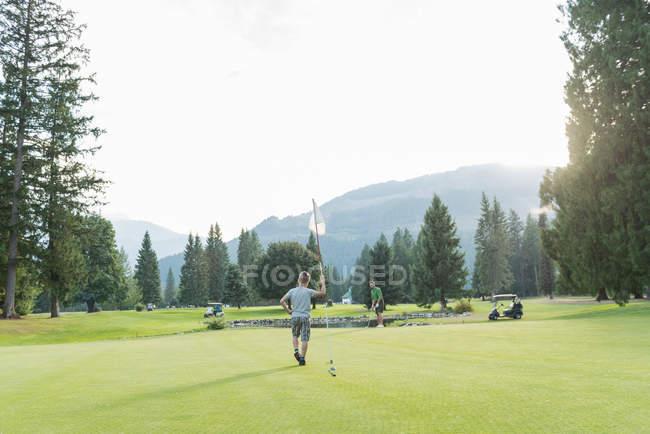 Отец и сын играют в гольф на поле — стоковое фото