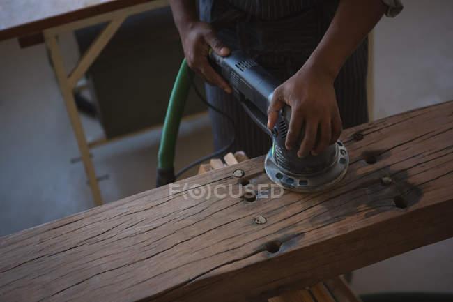 Середине раздел Карпентер, выравнивание древесины с полировальная машина в мастерской — стоковое фото