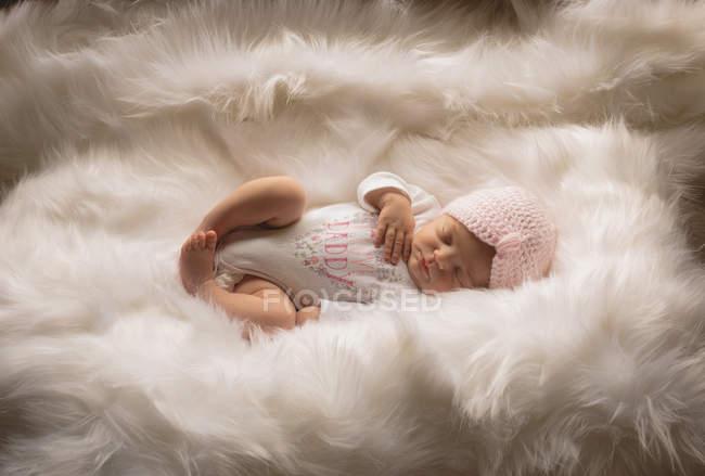 Новорожденного вязаная шапка, спать на пушистый одеяло на дому. — стоковое фото