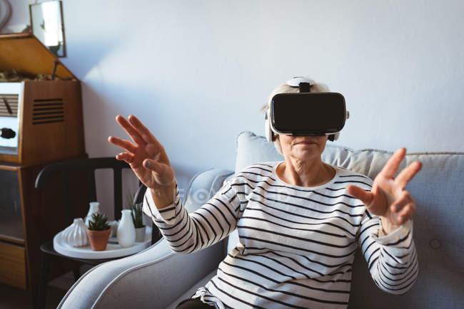Senior woman sitting on sofa wearing virtual reality headset at home — Stock Photo