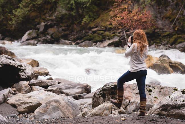 Vista posteriore della donna che fotografa un ruscello che scorre — Foto stock