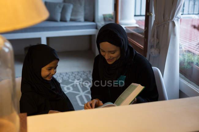 Мусульманська матері, допомагаючи її дочка читати Священного Корану вдома — стокове фото