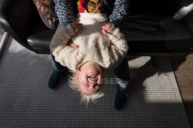 Père jouant avec sa fille dans le salon sur le canapé . — Photo de stock