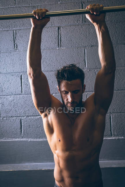 Muscular man exercising on pull-up bar in the fitness studio — Stock Photo