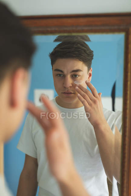Hombre aplicando crema facial delante del espejo en casa . - foto de stock