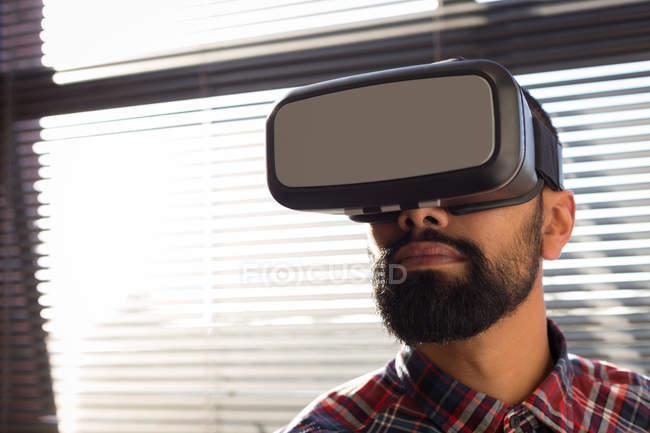Male executive using virtual reality headset in office — Stock Photo