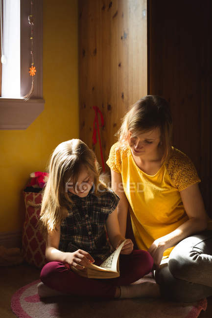 Daughter with mother reading a book in bedroom at home — Stock Photo