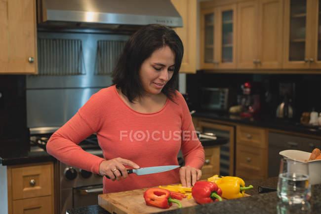 Legumes de corte de mulher na cozinha em casa — Fotografia de Stock