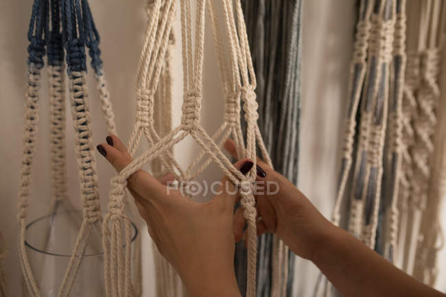 Cropped image of woman knotting strings in workshop — Stock Photo