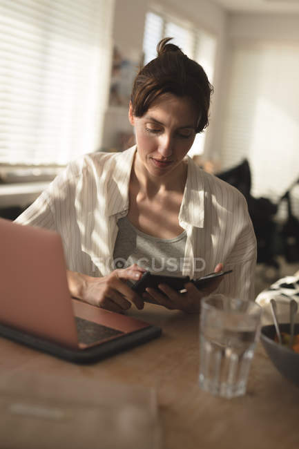 Young woman using her mobile phone besides her laptop at home — Stock Photo