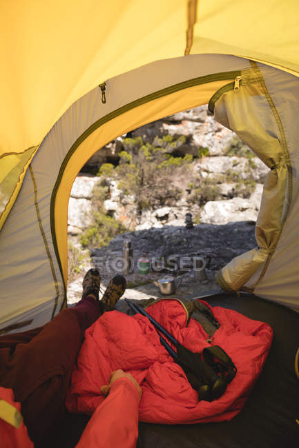 Hiker lying in a tent with camping equipment on a sunny day — Stock Photo