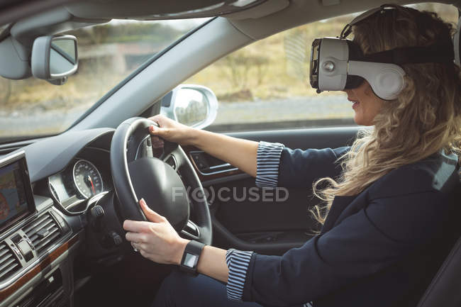Side view of female executive using virtual reality headset while driving a car — Stock Photo