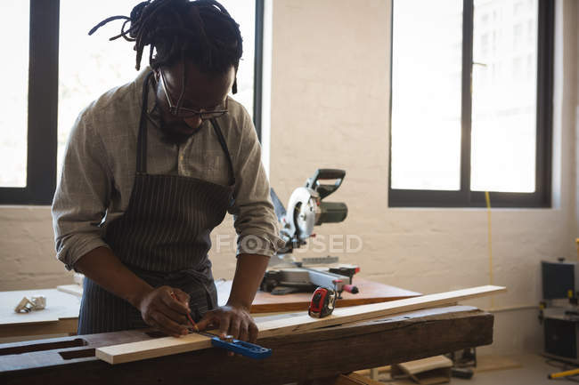 Carpenter measuring wooden plank with scale in workshop — Stock Photo