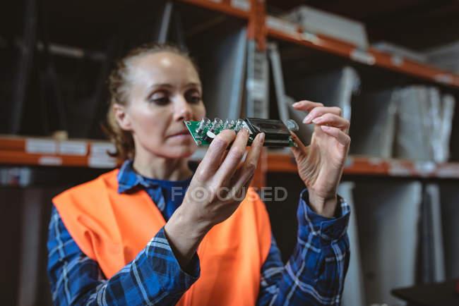 Arbeiterin überprüft Leiterplatte in Fabrik — Stockfoto