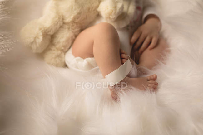 Cropped view of newborn baby sleeping with rabbit plush toy. — Stock Photo