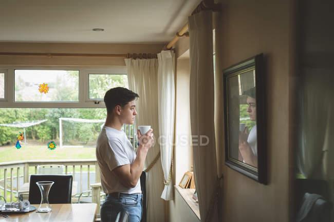 Giovane uomo che beve caffè guardando attraverso la finestra a casa . — Foto stock