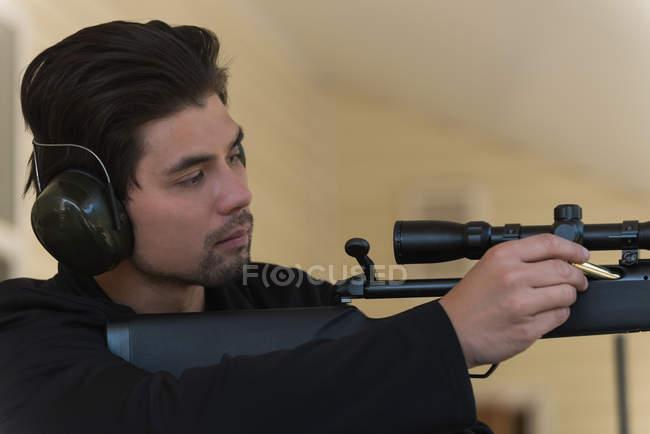 Gros plan de l'homme chargeant une balle dans un fusil de sniper — Photo de stock