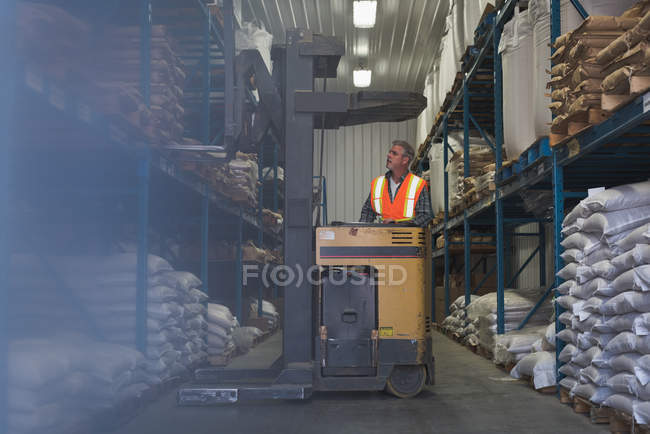 Man lifting sack of grains with forklift in factory — Stock Photo